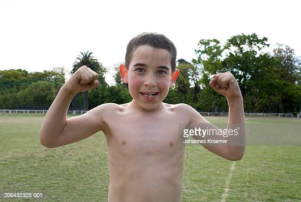 Boy (6-8) flexing muscles on field, portrait, close-up