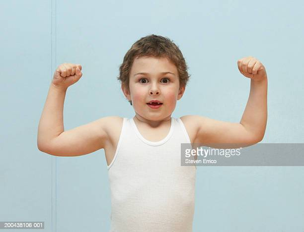Boy (5-7) flexing muscles, portrait