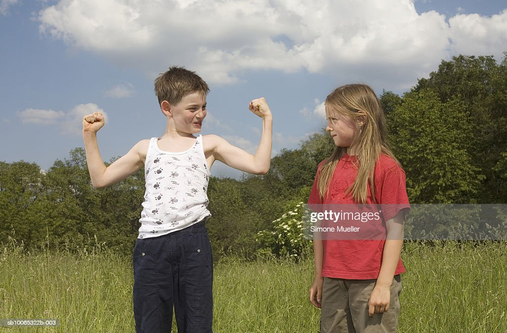 Boy (8-9 years) flexing muscles standing by girl (8-9 years) on meadow : Foto stock