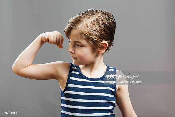 boy flexing muscles while standing against wall at home - flexing muscles stock pictures, royalty-free photos & images