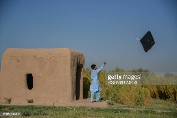 Boy flies a kite next to an earthen structure at a field on the outskirts of Herat on September 21, 2021.