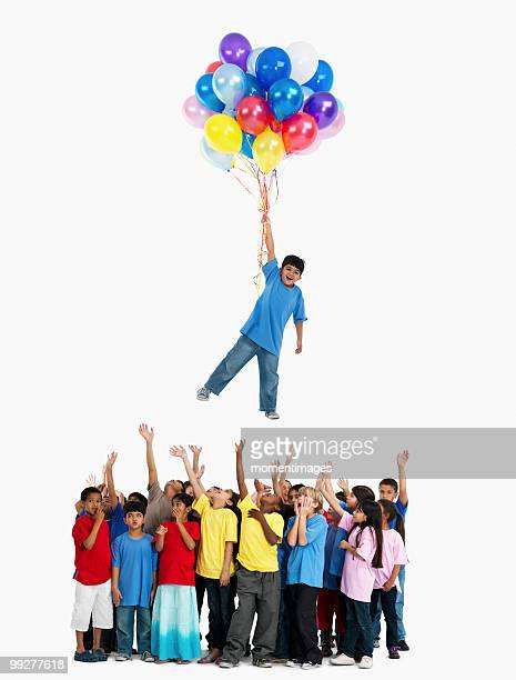 Boy floating away with balloons
