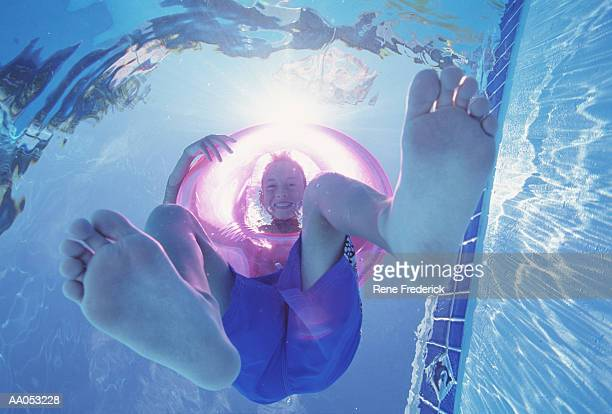 boy (10-12) floating in innertube in swimming pool, view from below - only boys stock photos and pictures