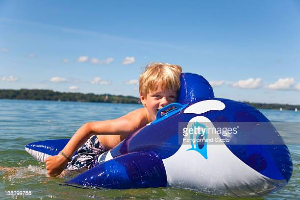 Boy floating in lake with toy whale