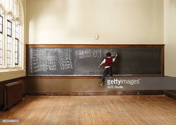 boy (8-9) floating on skateboard in classroom - school detention stock pictures, royalty-free photos & images