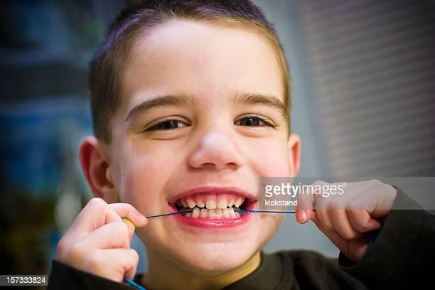 Menino flosses Dentes