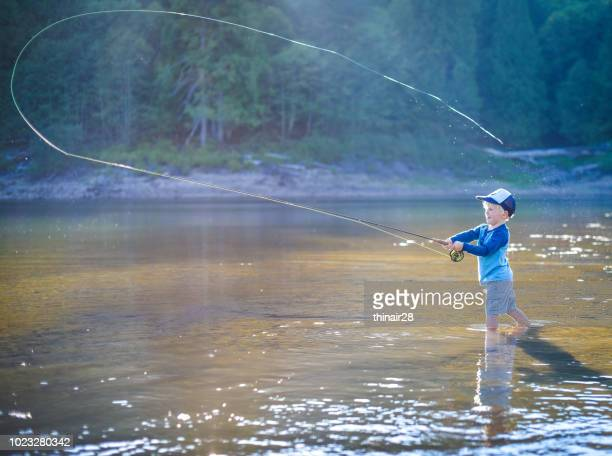 boy fly fishing - fly fishing stock photos and pictures