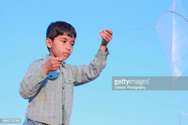 a boy flying a kite - cute pakistani boys stock photos and pictures