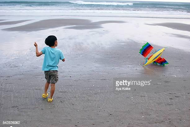 A boy flying a rainbow ship kite