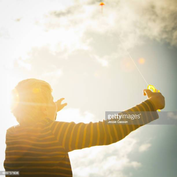 Boy flying kite looking up at the sky