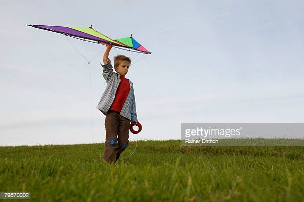 Boy (10-12) flying kite