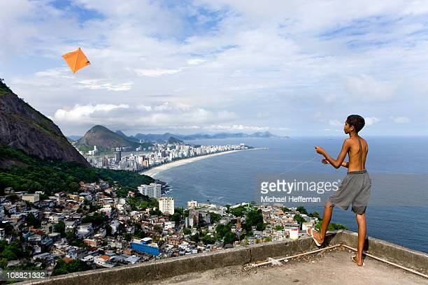 Boy flying kite with panorama of Rio.