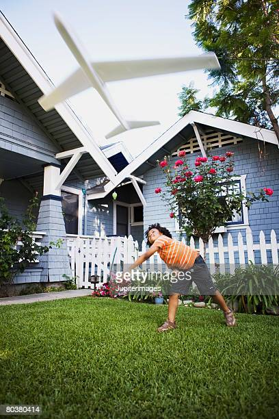 Boy flying toy airplane in front yard of house