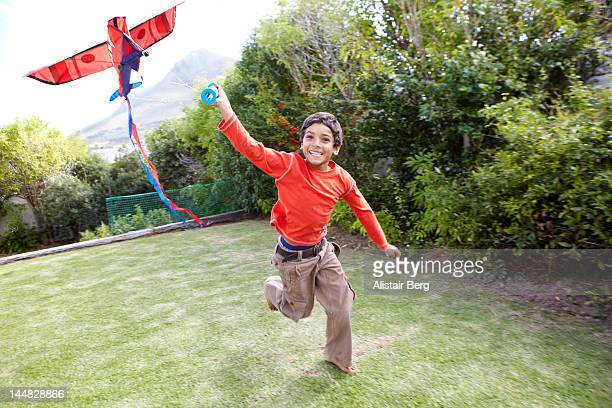 Boy flying toy kite in a garden