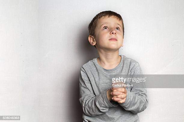 Boy folds his hands in prayer looking up