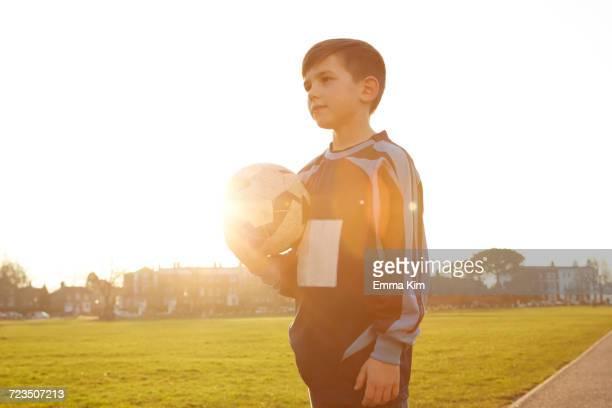 Boy football player holding ball in sunlit park