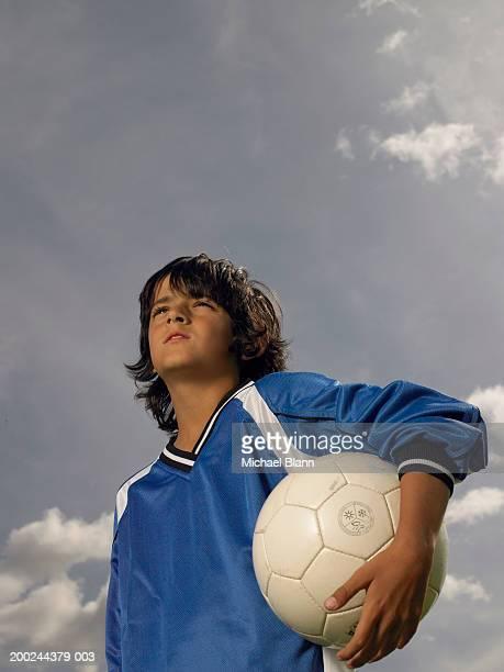 boy (8-10) footballer holding ball under arm, low angle view - axila fotografías e imágenes de stock