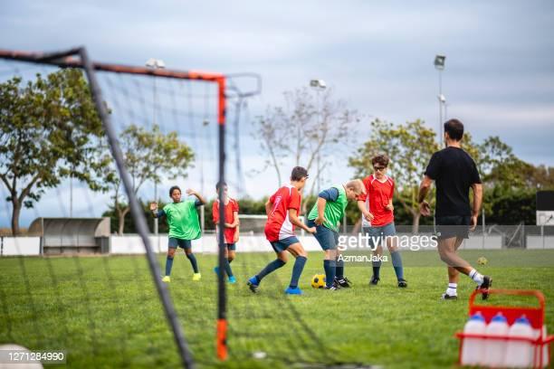 jungen fußballer im alter von 11-16 jahren spielen übungsspiel - jugendmannschaft stock-fotos und bilder