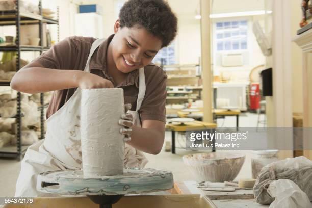 Boy forming pottery on wheel in studio