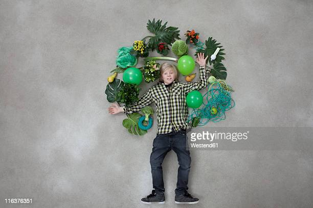 Boy forming tree shape on gray background