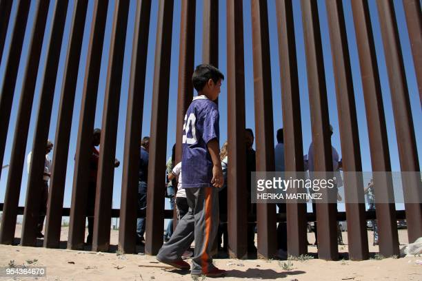 A boy from the Anapra area observes a binational prayer performed by a group of religious presbyters by migrants on the border wall between Ciudad...