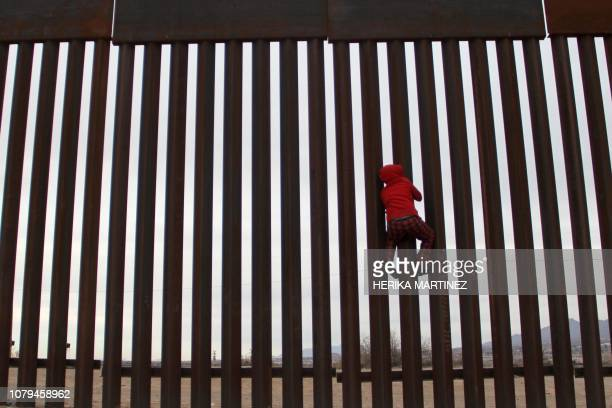 TOPSHOT A boy from the Anapra area playing climbs the border fence between Sunland Park New Mexico US and Ciudad Juarez Chihuahua state Mexico on...
