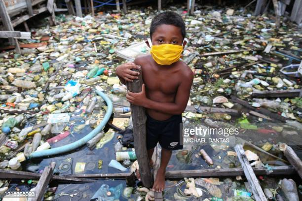 Boy from the Educandos riverside community wears a face mask during the COVID-19 coronavirus pandemic in Manaus, the Amazon on May 26, 2020. - The...