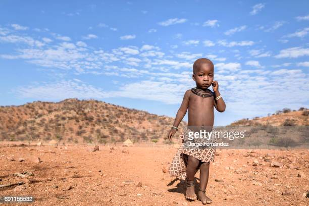 Boy from the Himba tribe walking barefoot on the harsh ground of the Kunene region