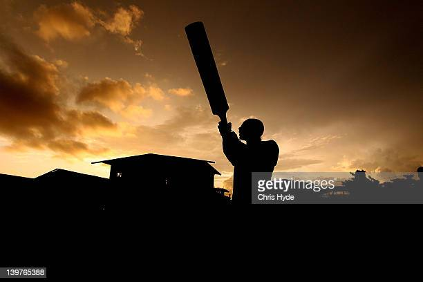 A boy from the village of Hanuabada bats during a game of cricket in the streets on February 24 2012 in Port Moresby Papua New Guinea