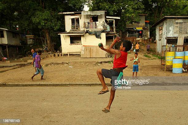A boy from the village of Hanuabada bowls during a game of cricket in the streets on February 24 2012 in Port Moresby Papua New Guinea