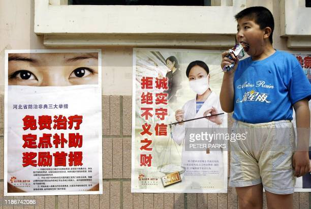 A boy from Yin Yi Dai village in Hebei province eats an icecream next to posters warning of SARS 28 May 2003 Many villages in this province which...