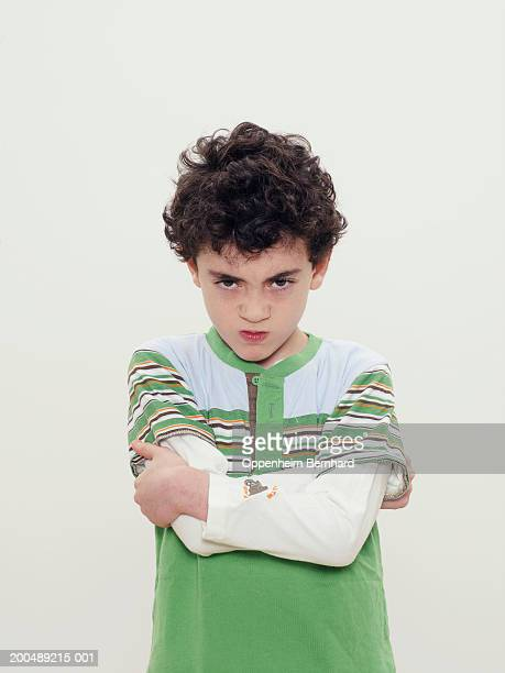 Boy (7-9) frowning, arms folded, portrait