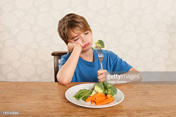 Boy frowning at vegetables