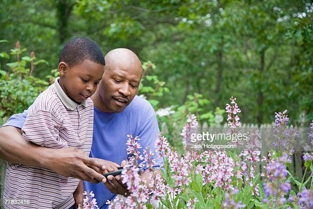 Boy gardening with the help of his father