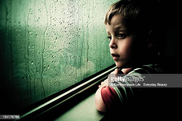 Boy gazes out of rain covered window