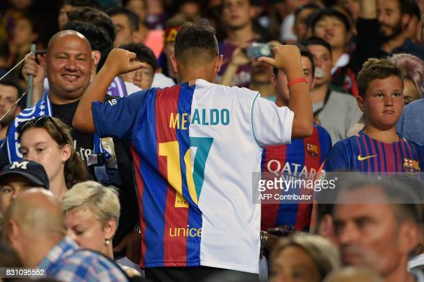 A boy gestures as he sports a jersey made with Barcelona's Argentinian forward Lionel Messi's jersey and Real Madrid's Portuguese forward Cristiano...
