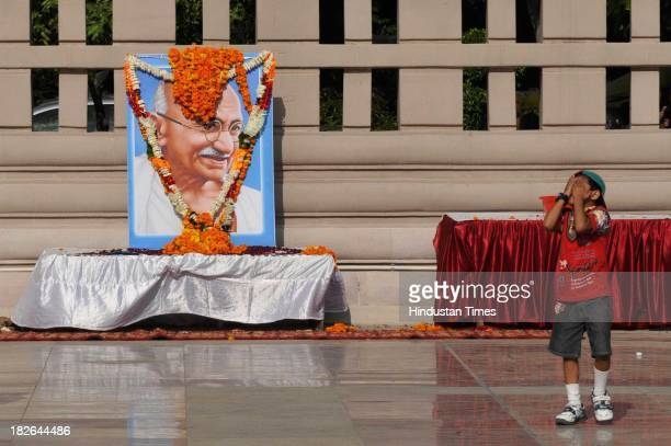 A boy gestures near the portrait of Mahatma Gandhi on the occasion of his 144th birth anniversary on October 2 2013 in Noida India Prime Minister...