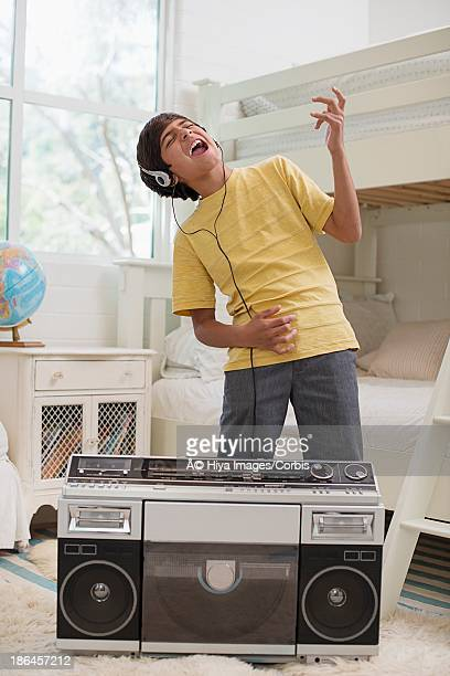 Boy gesturing while listening to music from old radio