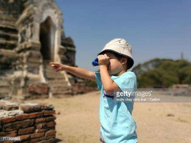 Boy Gesturing While Looking Through Binoculars At Historic Place