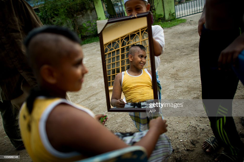 A boy gets a hair cut look in the mirror at the Iqro Al-Quran Bestari Academy for the orphanage in the suburbs of Kuala Lumpur on November 7, 2012.