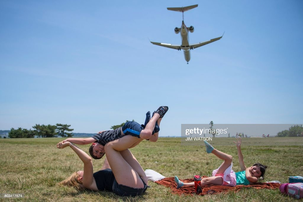A boy(C) gets an airplane ride from his nanny Celeste Pierrot (L) as his sister plays in Gravelly Point Park as planes land at Ronald Reagan National Airport in Arlington, Virginia on June 29, 2017. - President Donald Trump's travel ban on people from six mostly Muslim countries will come into force late Thursday, as controversy swirls over who qualifies for an exemption based on family ties.