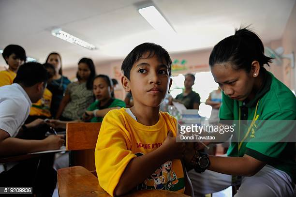 A boy gets vaccine shots by a nurse on April 4 2016 in Manila Philippines The Philippines launched its first public immunization program for dengue...