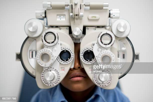 Niño para un examen de la vista en la óptica