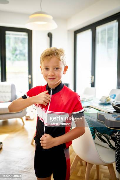 boy getting dressed zipping up his cycling top getting ready for a bike ride - saltdean stock pictures, royalty-free photos & images