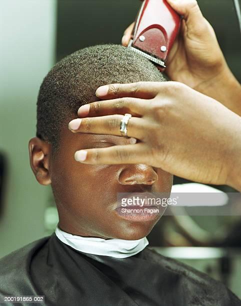 Boy (12-14) getting haircut in barbershop, close-up