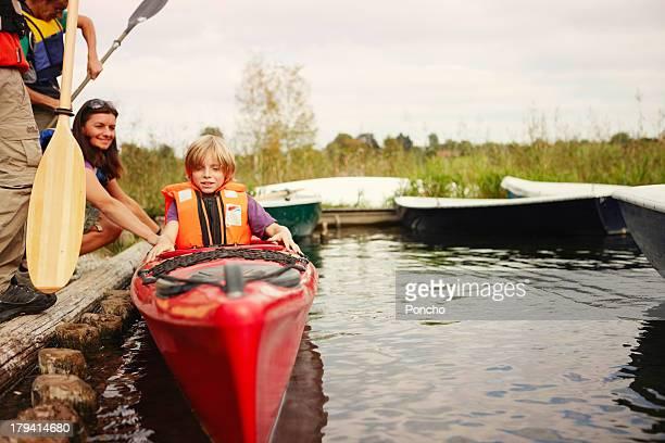 Boy getting into a canoe