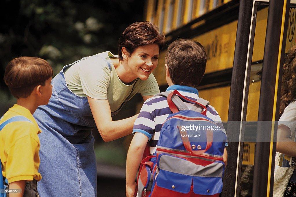 Boy getting on school bus : Stock Photo