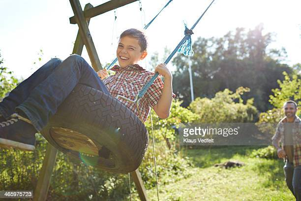 Boy getting pushed on swing, by his father