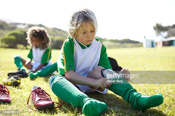 boy getting ready to play football - caneleira roupa desportiva de proteção imagens e fotografias de stock