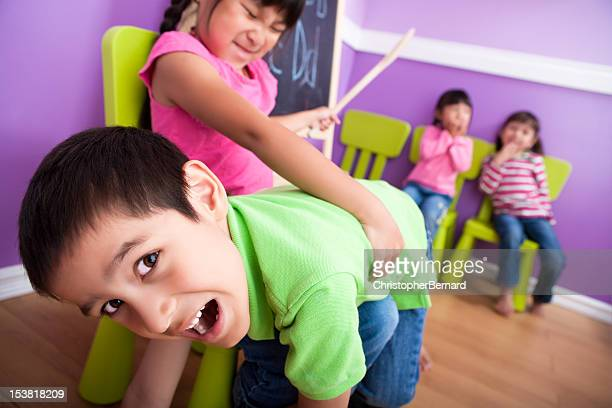 boy getting spank in class - spanking stock photos and pictures